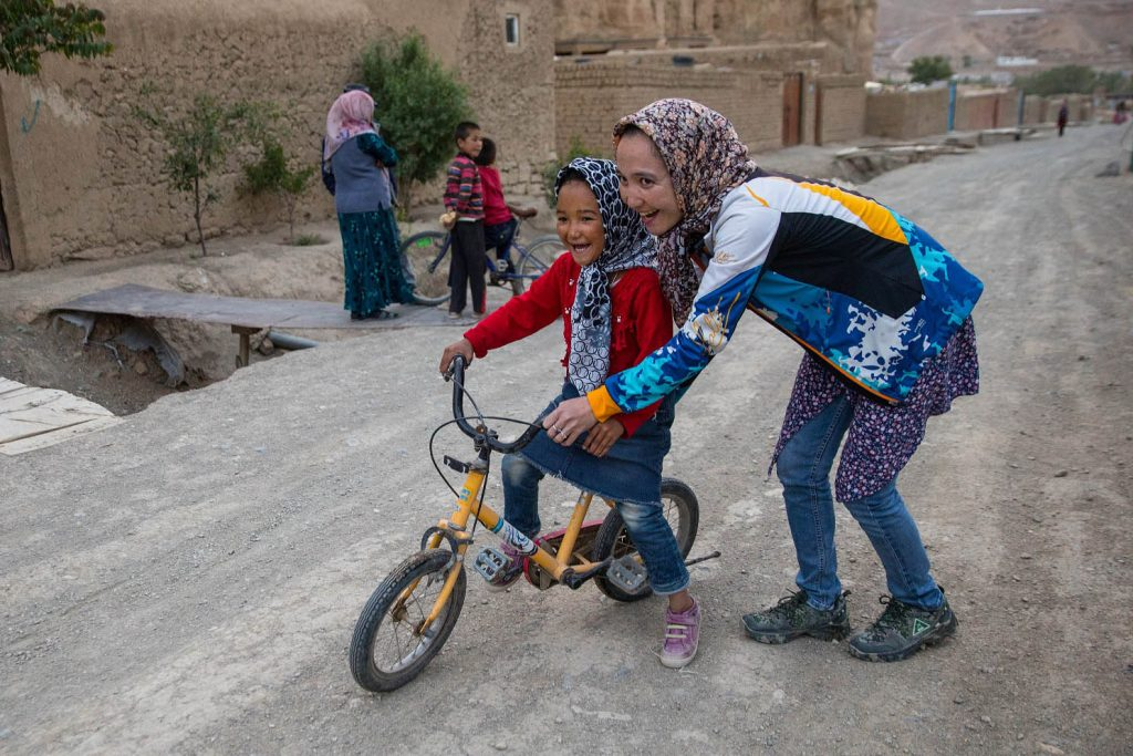 BAMIYAN, AFGHANISTAN: Zakia Mohammadhi, age 23, pushes her youngest sister, Honey, age 7 on her bike infant of their home which is situated on a dirt road up a hill  that can be challenging for a child. Zakia started biking when she was 5 years old. Zakia is also part of the Bamiyan ski club, and is the first Afghan woman to paraglide, doing so in Bamiyan and in Kabul.   One of the safest and most beautiful places in Afghanistan is Bamiyan, home to the Buddhas of Bamiyan (4-5th century) destroyed by the Taliban in 2001. The Bamiyan women's cycling team was started by Zakia Mohammadhi which had only 2 girls in 2013, now it has around 12 members and is growing in popularity. It is the first official team outside of Kabul. The women did this on their own with no male support, it was girls teaching girls to ride, girls registering the team with the sports federation in Kabul, and girls organizing the first ever girls bike race in Afghanistan, and right to ride bike rides through Bamiyan with the male bike team supporting them along with the community.  Zakia organizes and coaches the team who ride daily either early morning and after school and work in the late afternoon. She also works closely with the Afghan Cycling Federation and the men's team in Kabul. Given the safe environment in this part of the country it allows the women the freedom to ride without the security threat that is the unfortunate reality in Kabul. The girls frequently ride in the mountains around Bamiyan, it is visually stunning, a very different scene from congested Kabul where the women are worried about angry men throwing rocks at them.